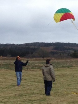 Scott launches a smaller kite while Ted looks on.